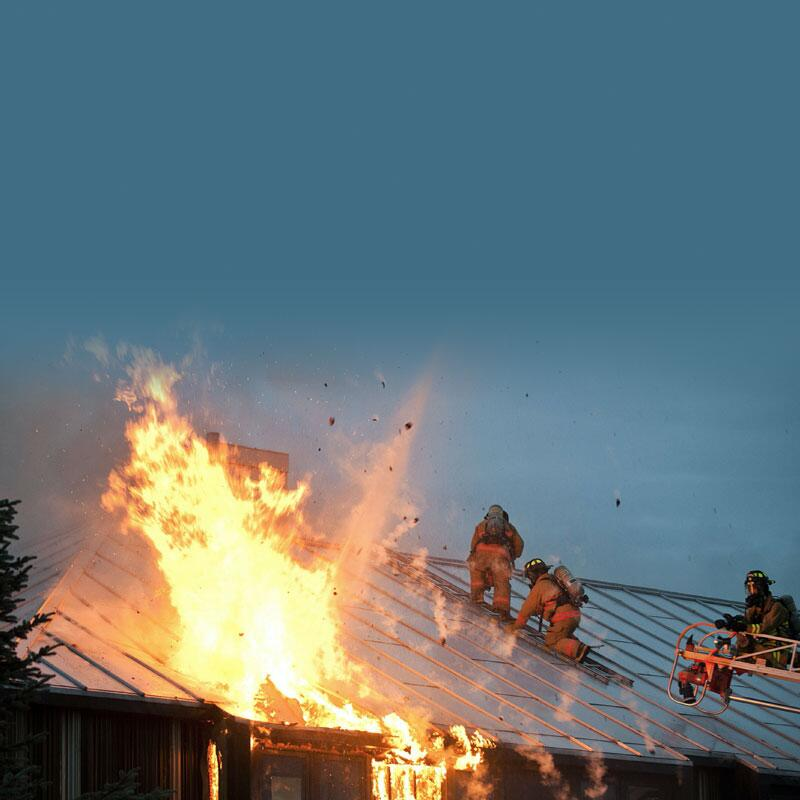 Photo of firemen on the roof of a house, fighting a fire.