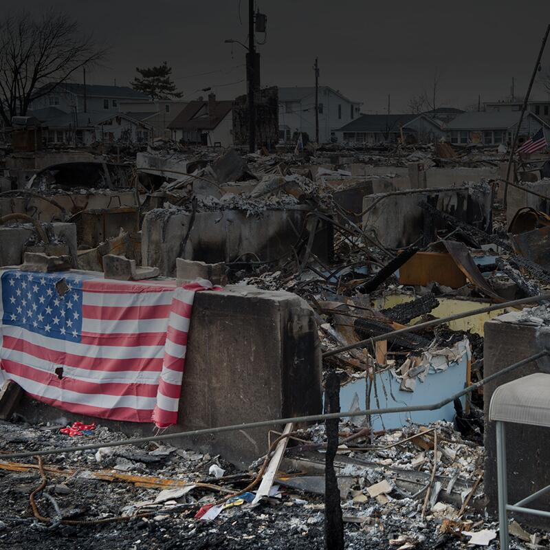 Decimated houses and rubble after hurricane Sandy, with an American flag drapped over the damage.