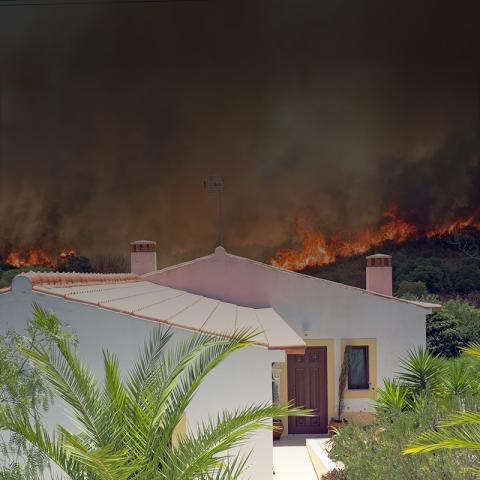 A wildfire burns in the background, moving close to a white house with a Spanish roof, that sits in the foreground.