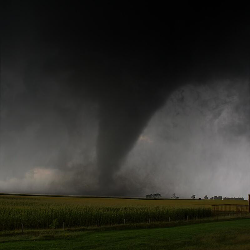 a tornado in the background of a farm with lots of fields.