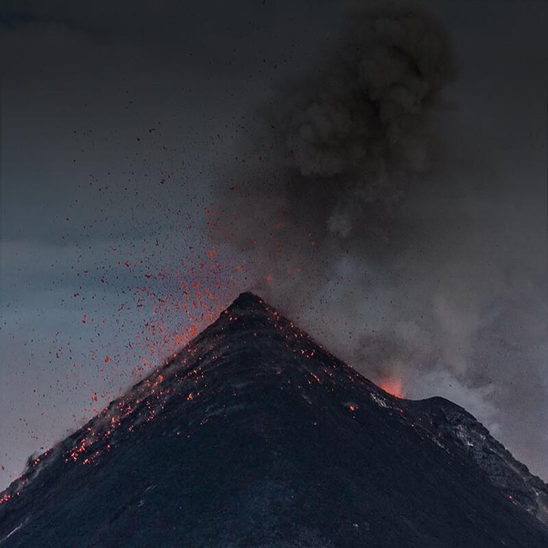 Image of an erupting volcano from up close with lava spouting everywhere and smoke coming from the top