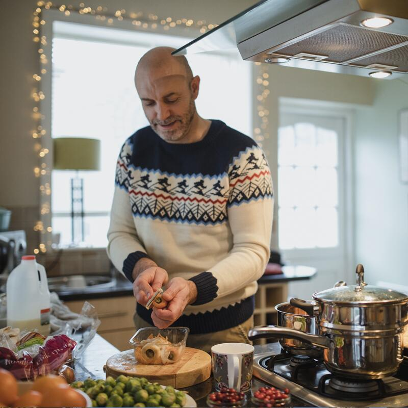 a man wearing a holiday sweater cooking a meal