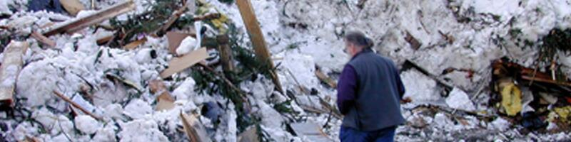 January 30th, 2000. A man looks through rubble covered in snow and ice.