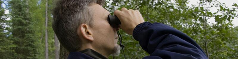 September 14th, 2003. A man peers through a pair of black binoculars.