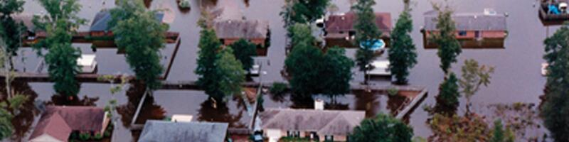July 2nd, 1994. An aerial view of a flooded neighborhood shows water reaching the second story of some homes.
