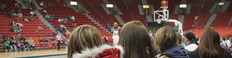 January 27th, 2009. A small group of college girls sit floor-side watching their school run through pre-game warm-ups.