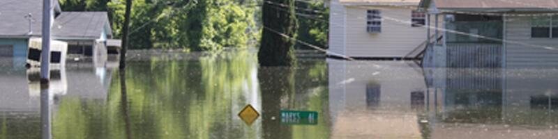 August 29th, 2005. Standing water floods the streets of Mississippi, measuring just under street signs.