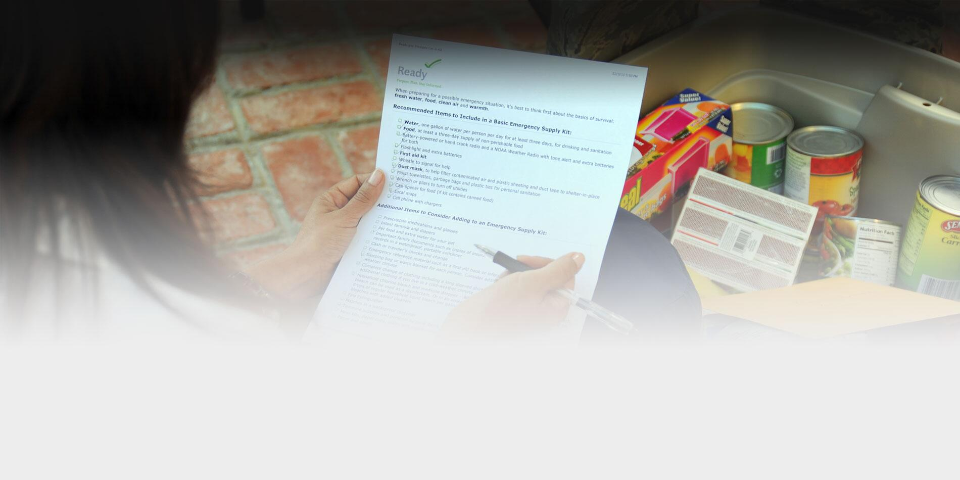 Close up picture of a woman holding an emergency supply kit checklist and compiling supplies into a bin.