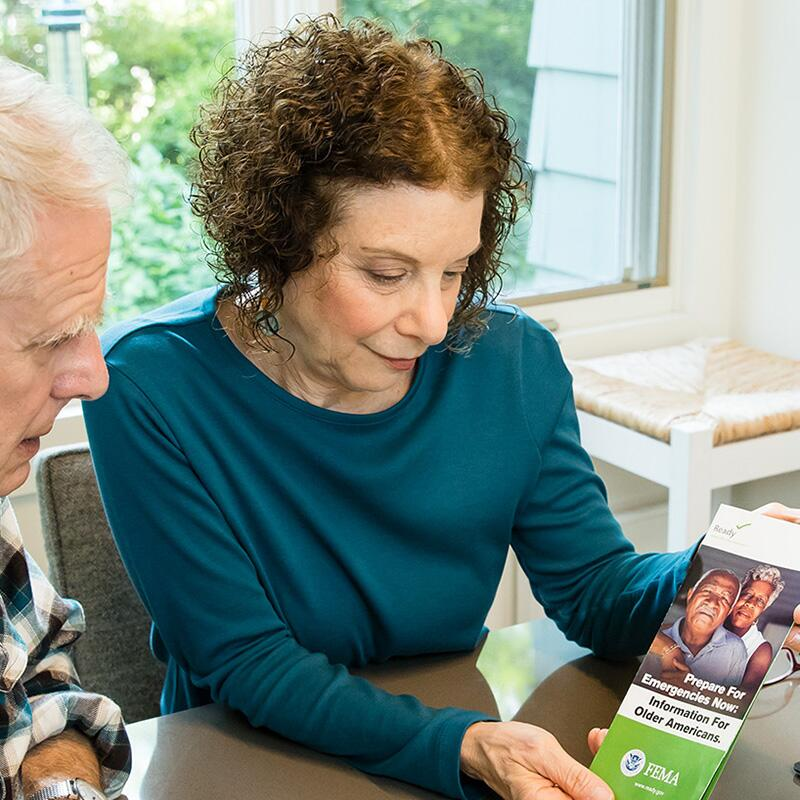 an older woman shows her husband a brochure on preparing for seniors
