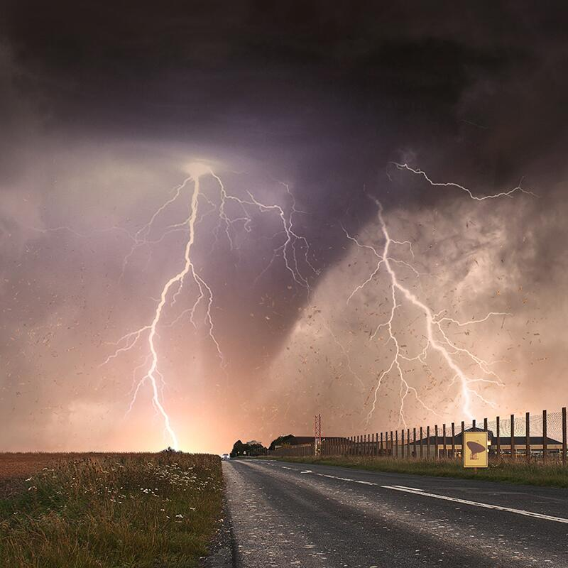a tornado and lightning in the distance of a long road
