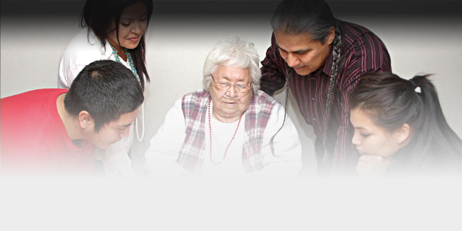 Picture of a multigenerational Native American family gathering around the grandmother at a table.