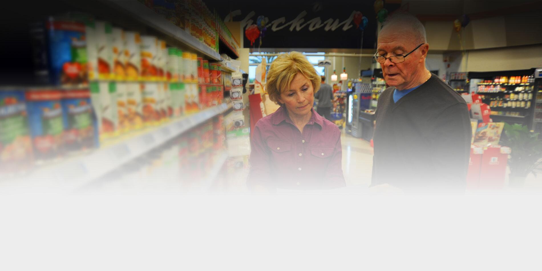 Picture of two seniors shopping in the grocery store from a list.