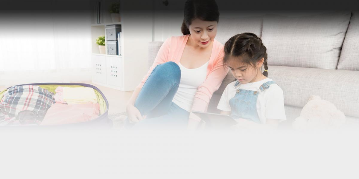 Picture of a mother and school age daughter looking at a tablet while packing clothes.