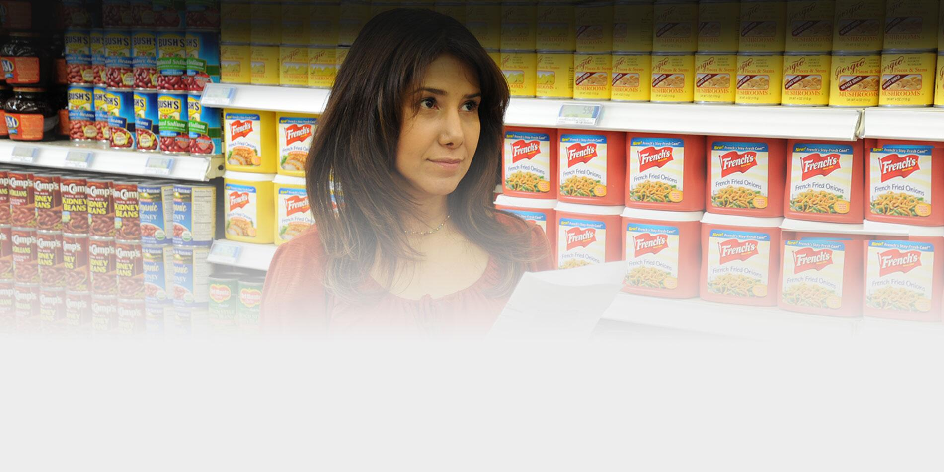 A picture of a woman shopping for food from a list in the grocery store.