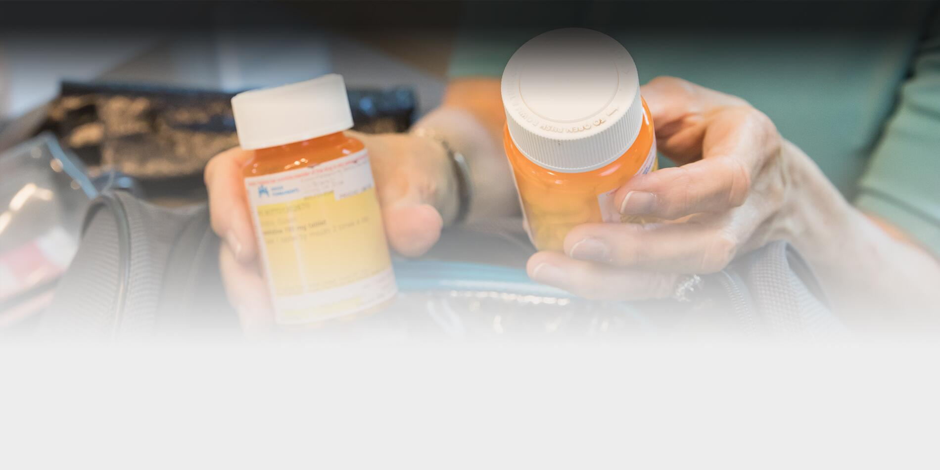 a close up picture of two hands holding bottles of perscription medications.