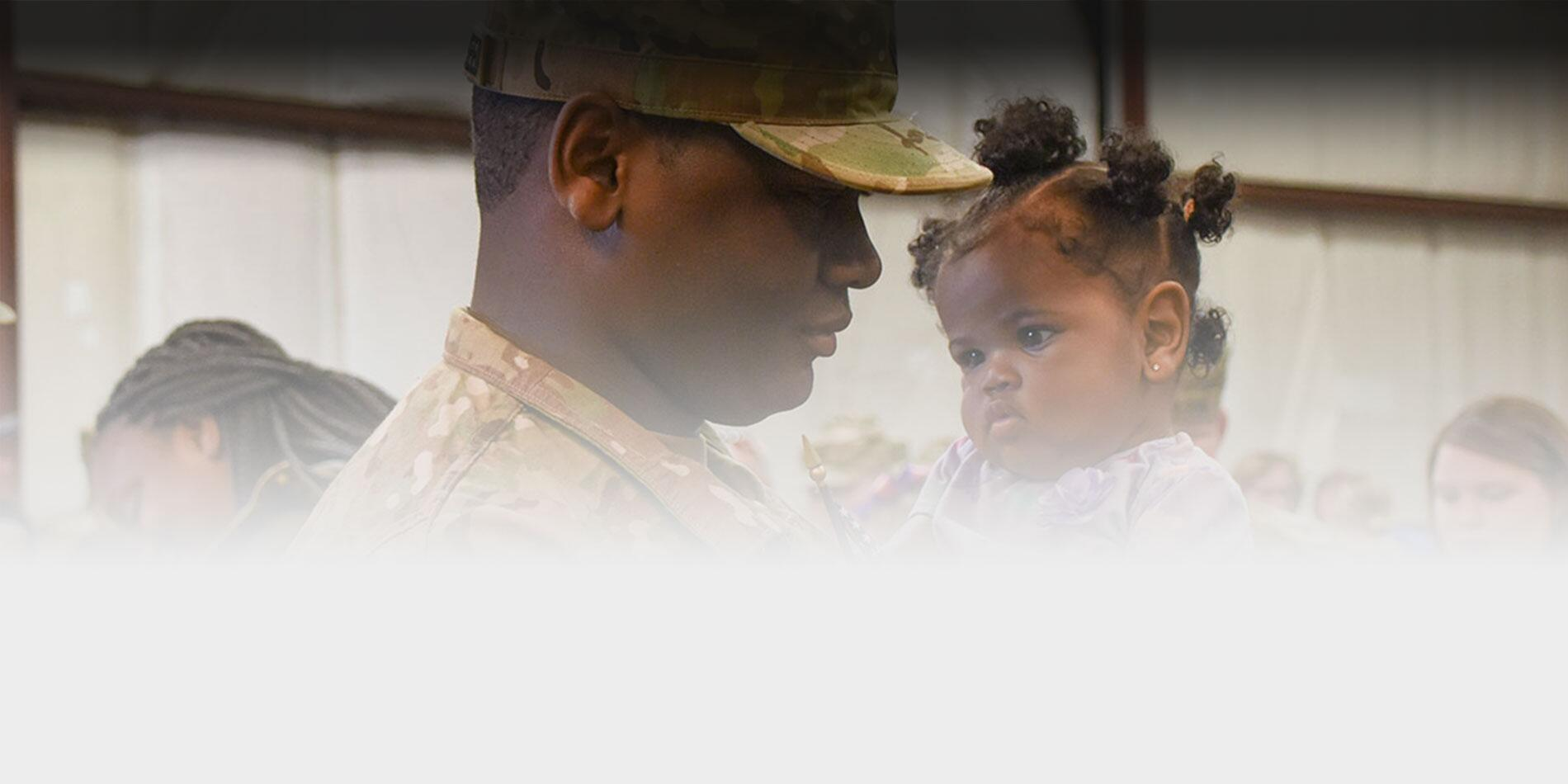 Picture of an army soldier holding his daughter.