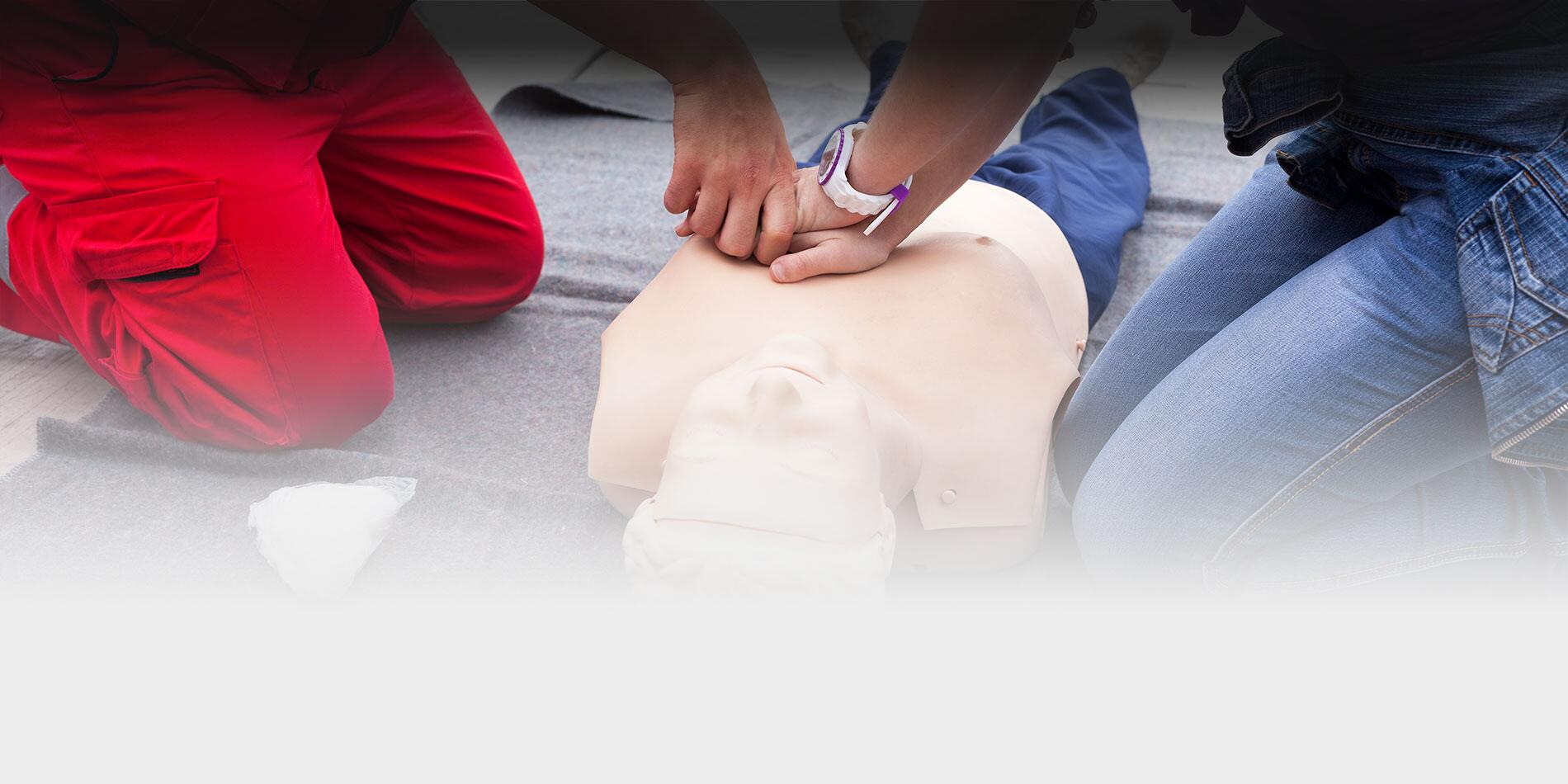 Close up photo of two people practicing CPR on a dummy.