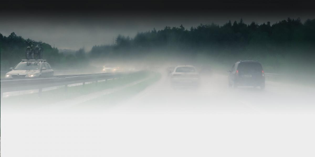 photo of cars on a highway during a foggy rain storm, going both directions.