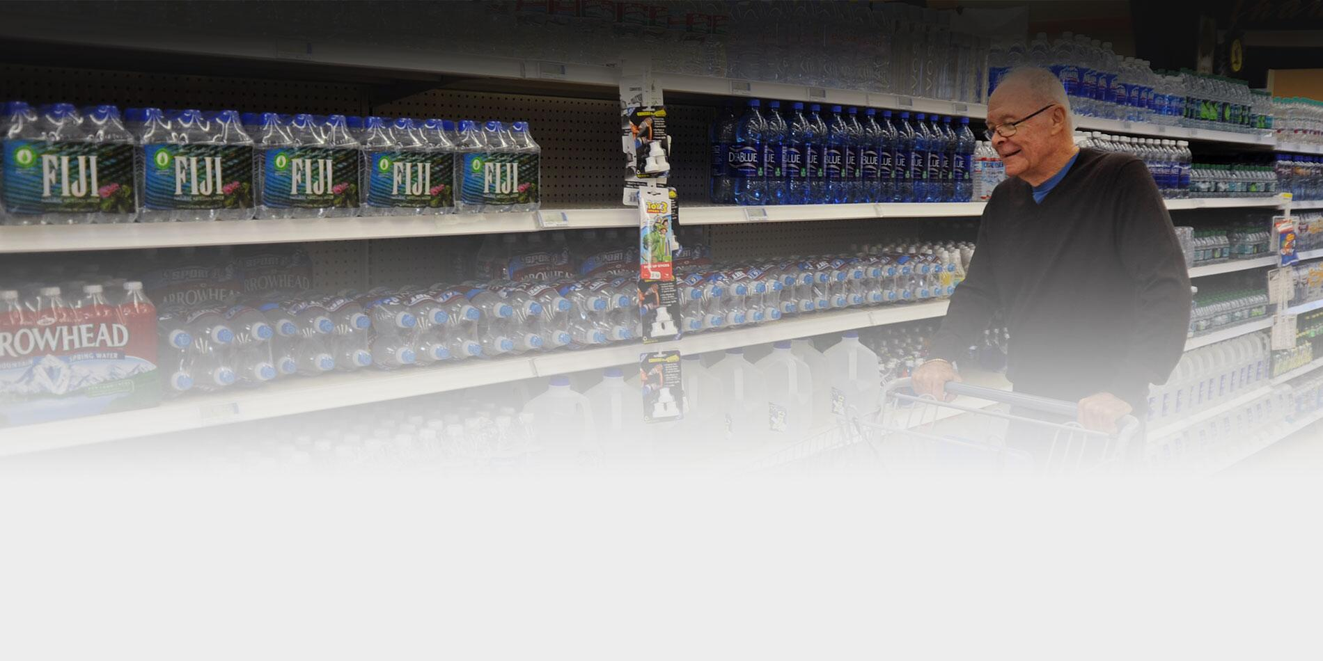 Picture of an elderly man shopping for water at the grocery store.