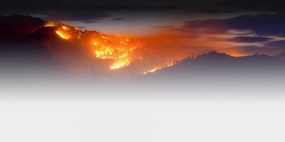 Picture of a large buring wildfire on a mountain at sunset.