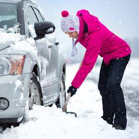 A woman digs her car out of the snow.