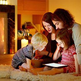 family sits inside by fire on a winter day.