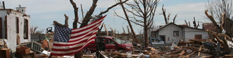 May 4th, 2007. A neighborhood of homes demolished by the tornadoes. An American flag hangs on a tree.