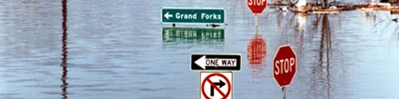 April 17th, 1997. Standing water floods the streets of Minnesota, measuring just under street signs.